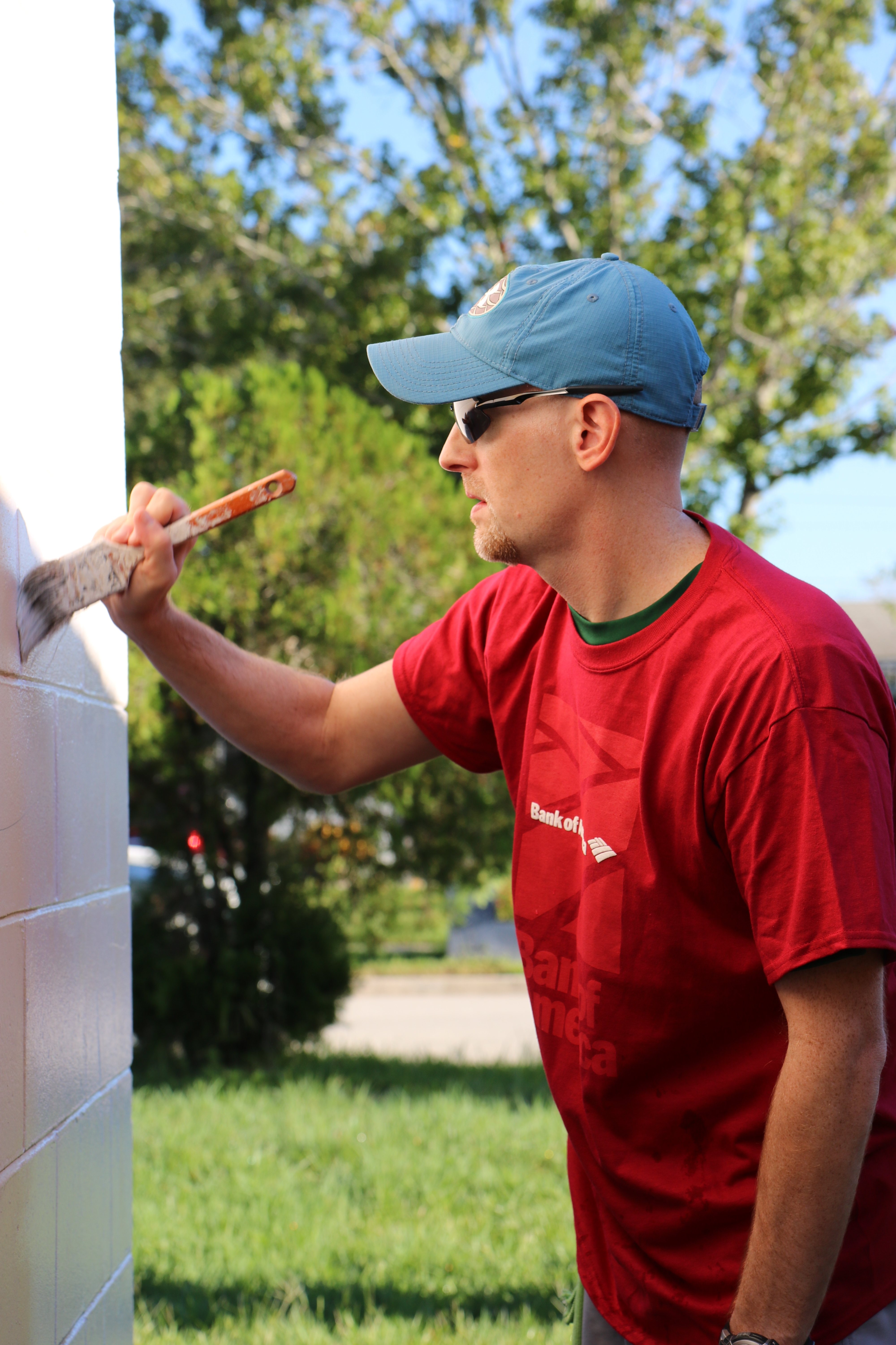 Man wearing baseball cap looking at the side of a house and painting