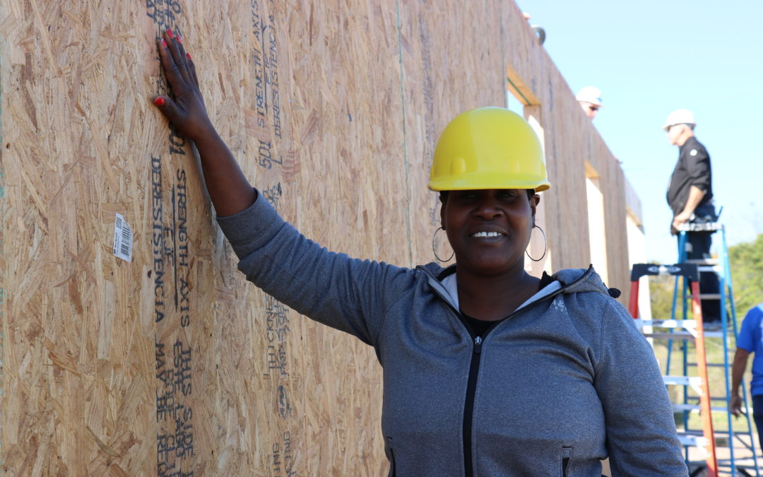 A Habitat Orlando & Osceola volunteer leans on the wall of a home that's under construction.