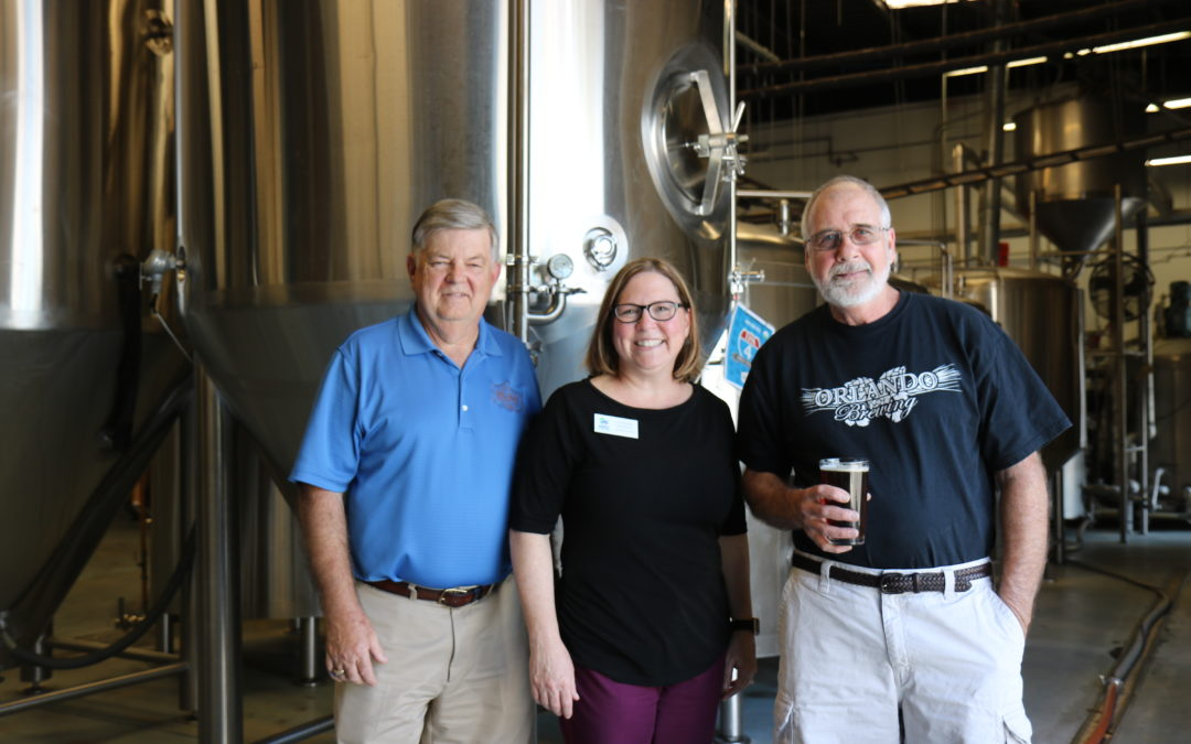 Habitat CEO Catherine McManus poses with two men from Orlando Brewing at the brewery.