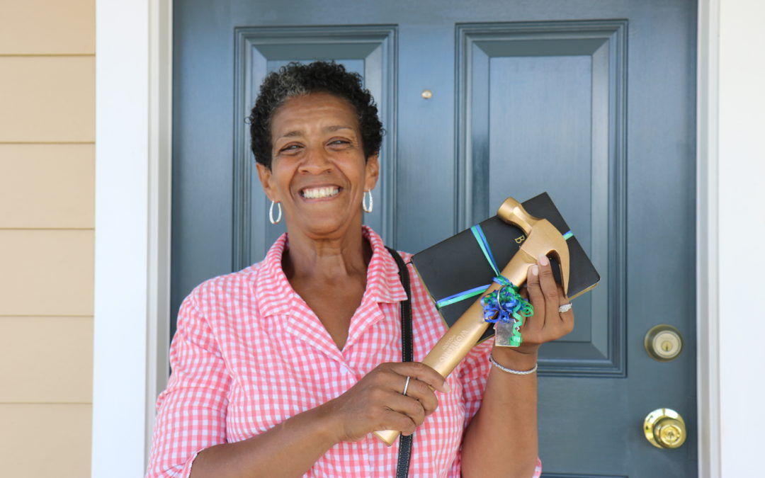 A Habitat homeowner poses in front of a blue door with a gold hammer and a bible.