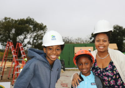 Woman and two boys wearing hard hats and smiling in front of in-progress house