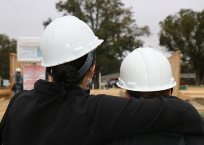 Two women embracing looking at walls being raised