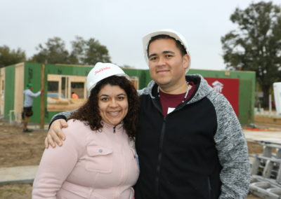 Man and woman smiling and standing in front of in-progress house