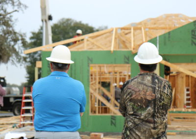 Two men wearing hard hats looking at in-progress house