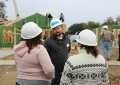 Women talking to man wearing hard hat in front of two under-construction homes