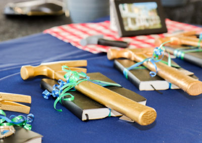 Close-up of golden hammers on top of black Bibles on blue tablecloth