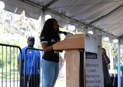 """Women standing at microphone on podium with """"Lowe's International Women Build Day"""" sign next to her"""