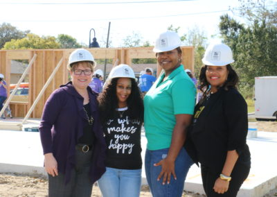 Four women wearing hard hats and smiling in front of in-progress home