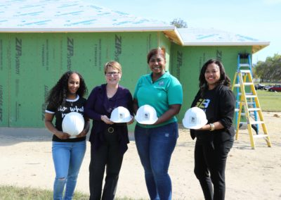 Four women holding hard hats and smiling in front of in-progress house