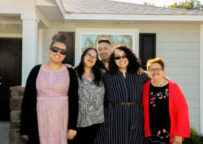 Family of five people smiling in front of completed house