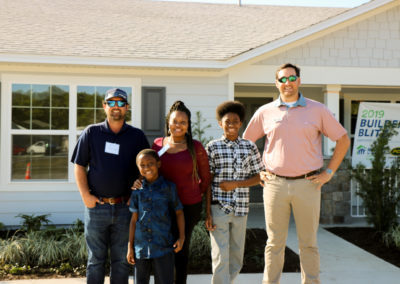 Two men, a women and two boys smiling in front of completed home