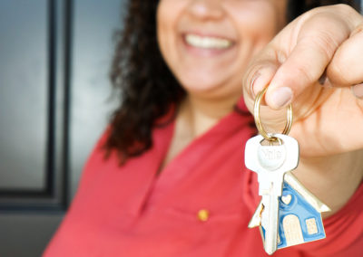 Woman smiling in front of black door and holding out house-shaped keychain