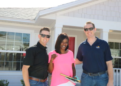 Two men and woman smiling in front of completed house