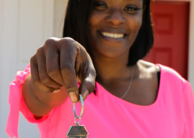 Woman smiling in front of red door holding out house-shaped keychain