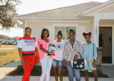 Five women smiling standing in front of completed house with open front door