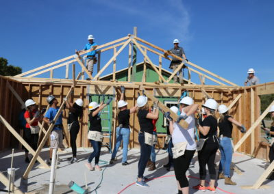 Group of women holding wooden beams to raise trusses