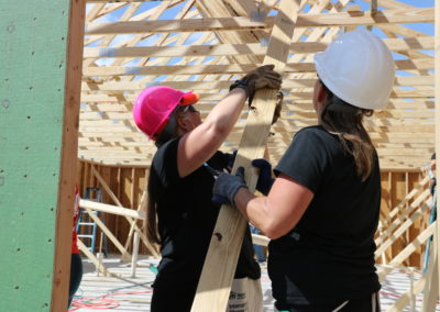 Two women wearing hard hats and raising wooden beam below trusses