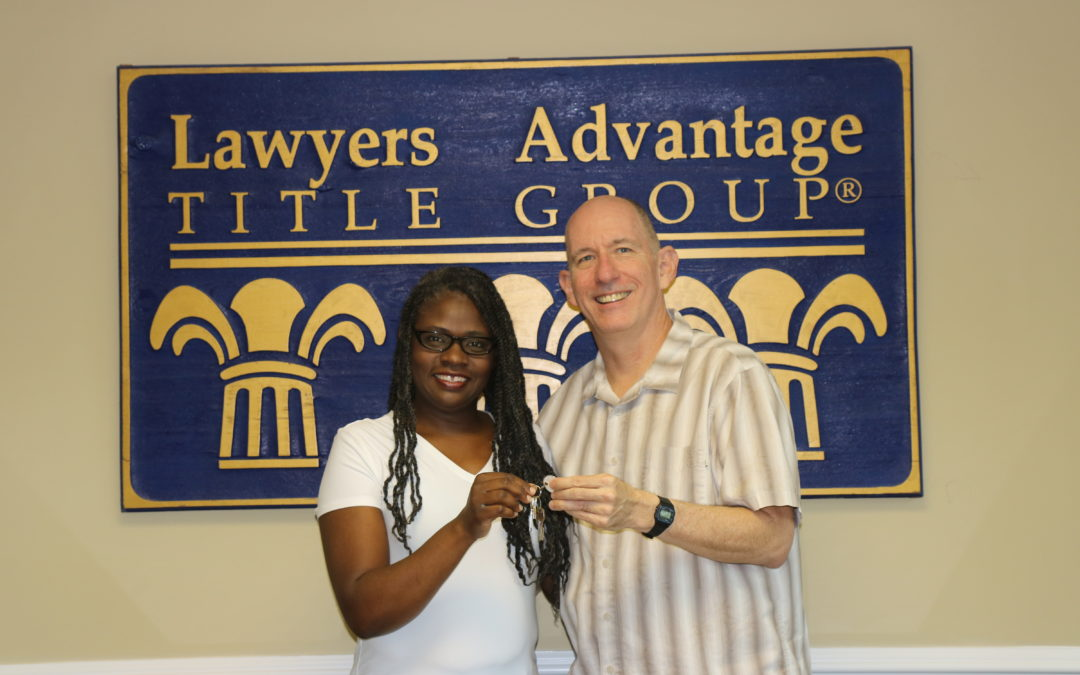 Woman and man smiling holding keys in front of Lawyers Advantage Title Group sign