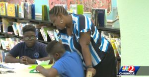 Future homeowner Wanda helps her two sons with their homework in a library.