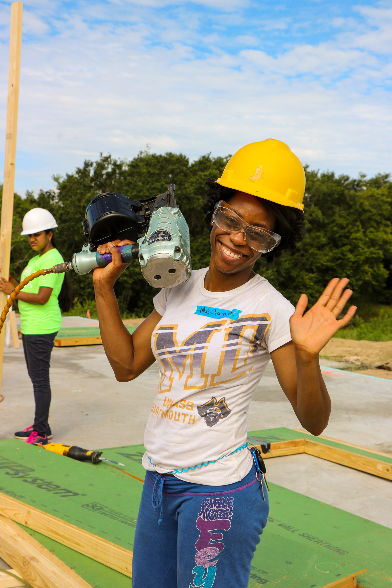 Smiling woman wearing construction hat and protective goggles and holding a nail gun