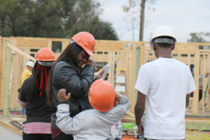 Family of a women, a teenager and two children wearing hard hats with unfinished home in background