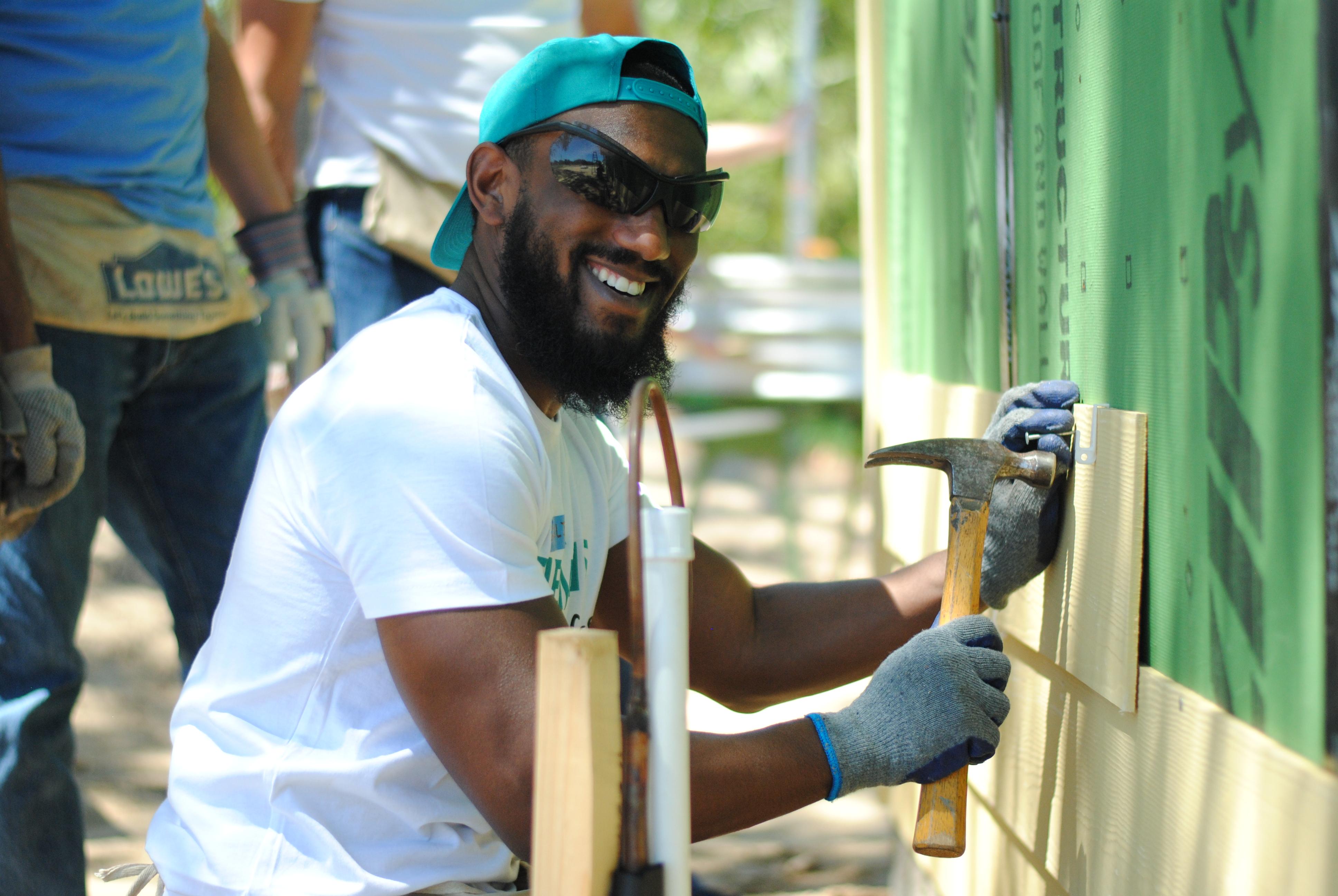 Smiling volunteer installing siding outside in-progress home