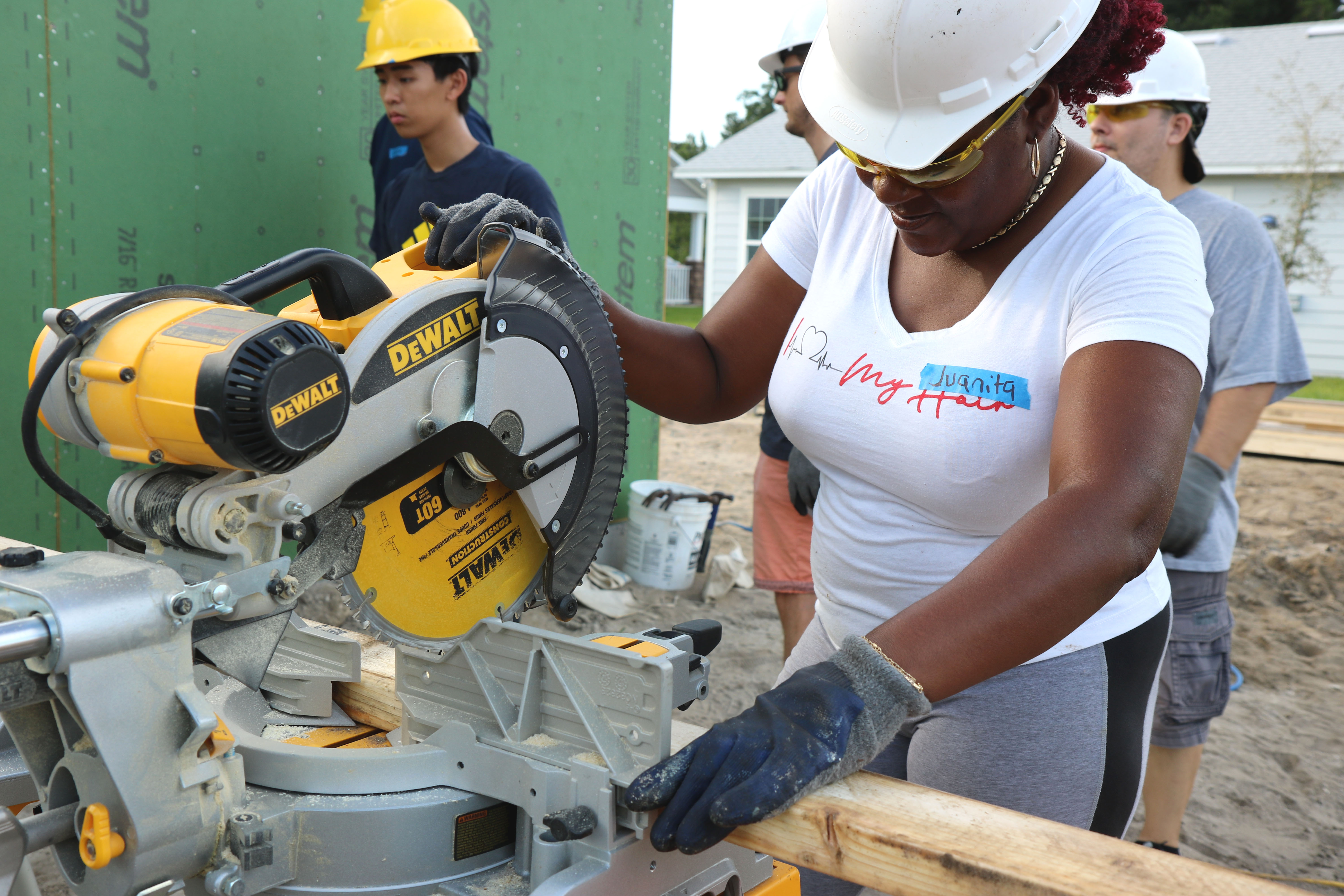 Woman wearing hard hats and glasses, using power saw on build site