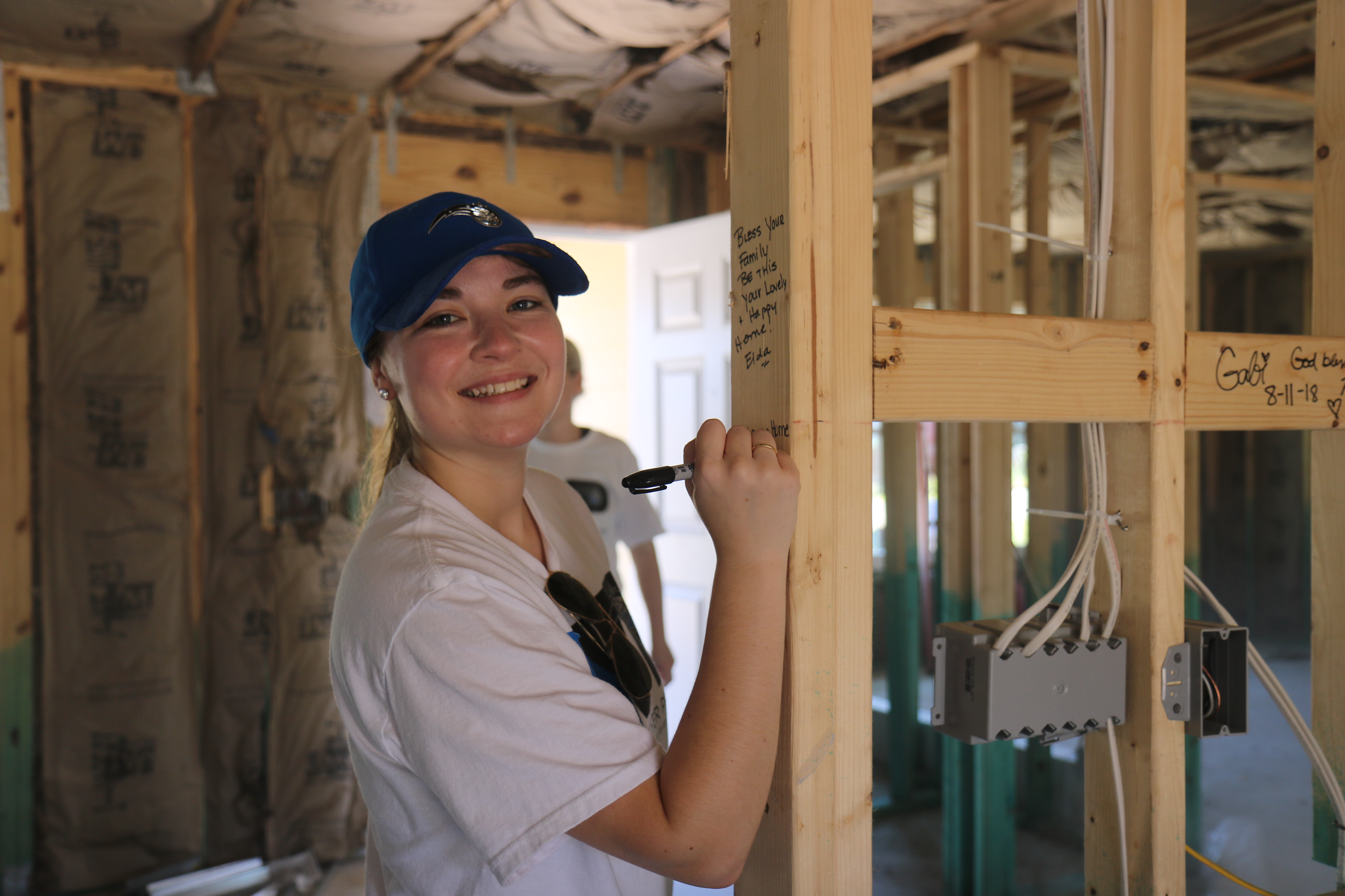 Smiling volunteer writing a blessing on interior beam of in-progress home