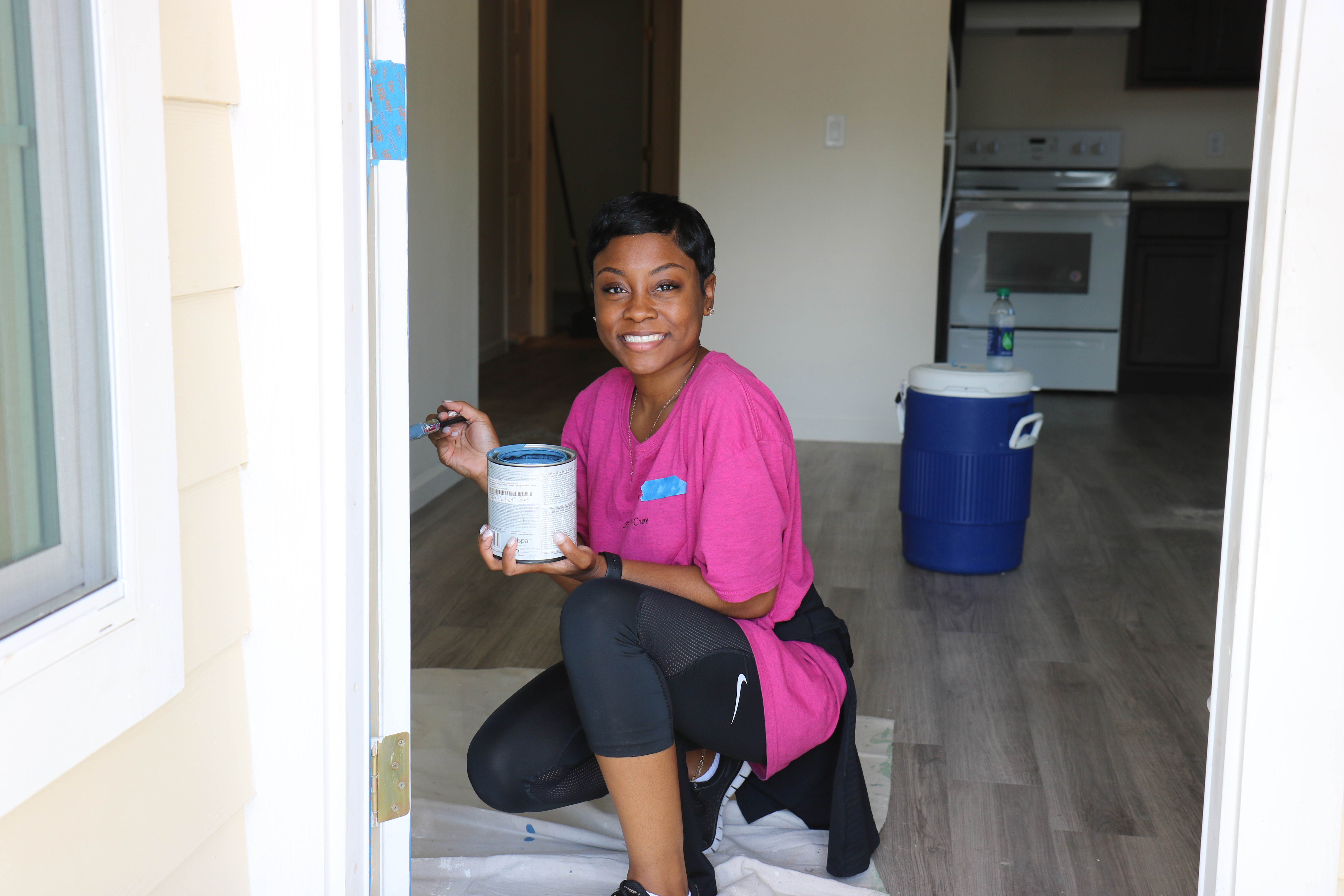 Smiling volunteer painting exterior door frame with blue cooler and kitchen in background