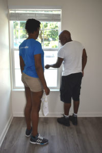 Crew leader Roman Ramesar shows a volunteer how to clean a window at a Habitat Orlando & Osceola build site.