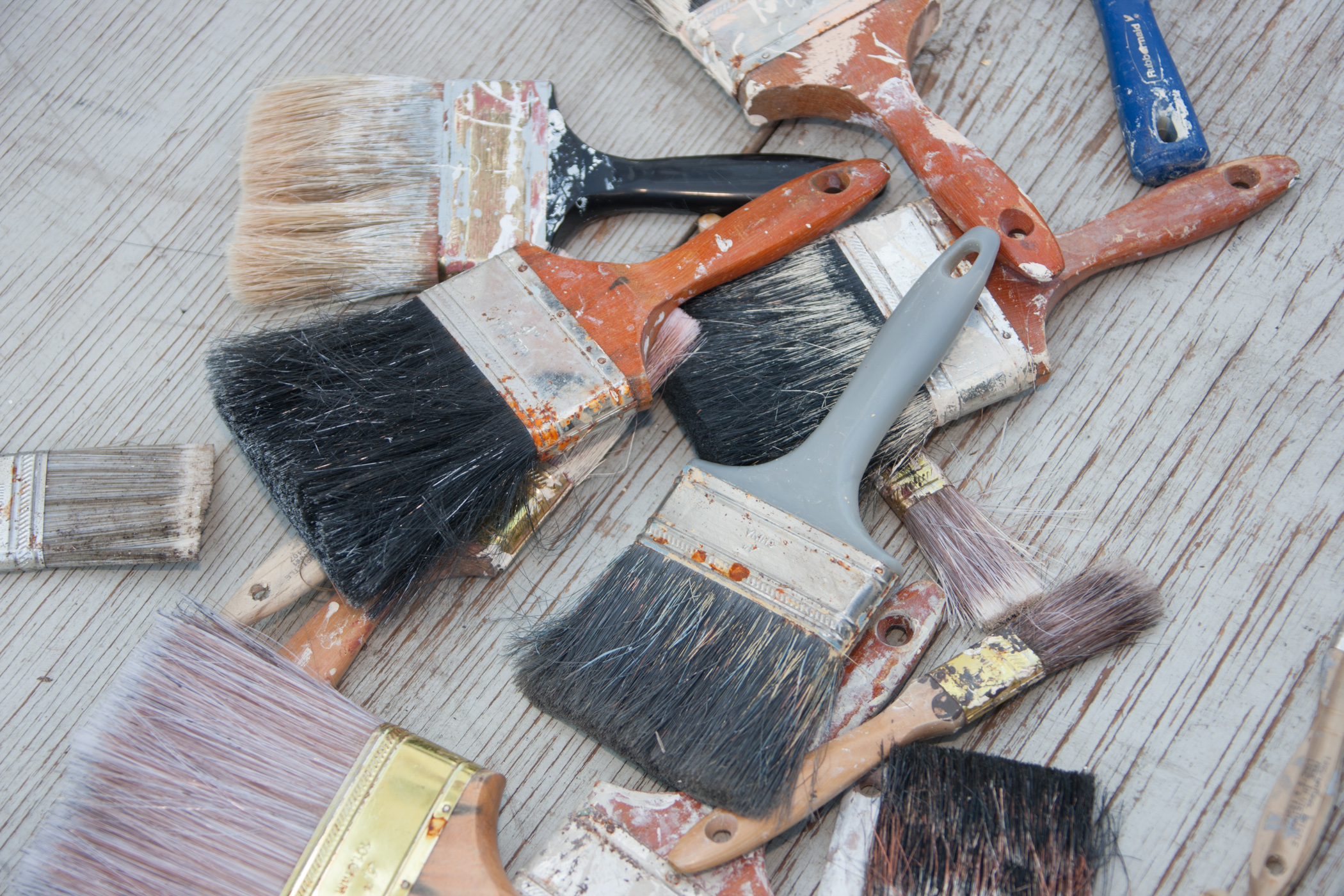 Various paintbrushes in a pile on wood background