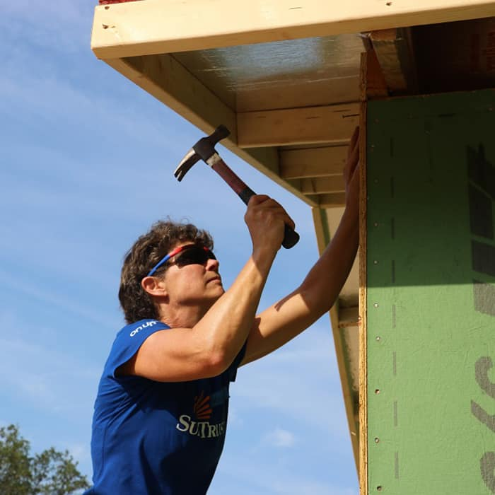 Woman wearing blue shirt looking up and holding hammer toward nail under eaves of unfinished house
