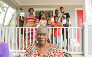 Vivian in front of her rebuilt home, with her family.