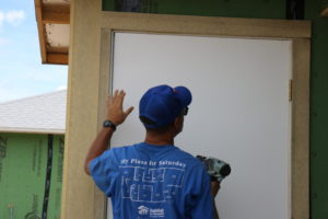 Crew leader Jose works on a Habitat Orlando & Osceola build site installing a door.