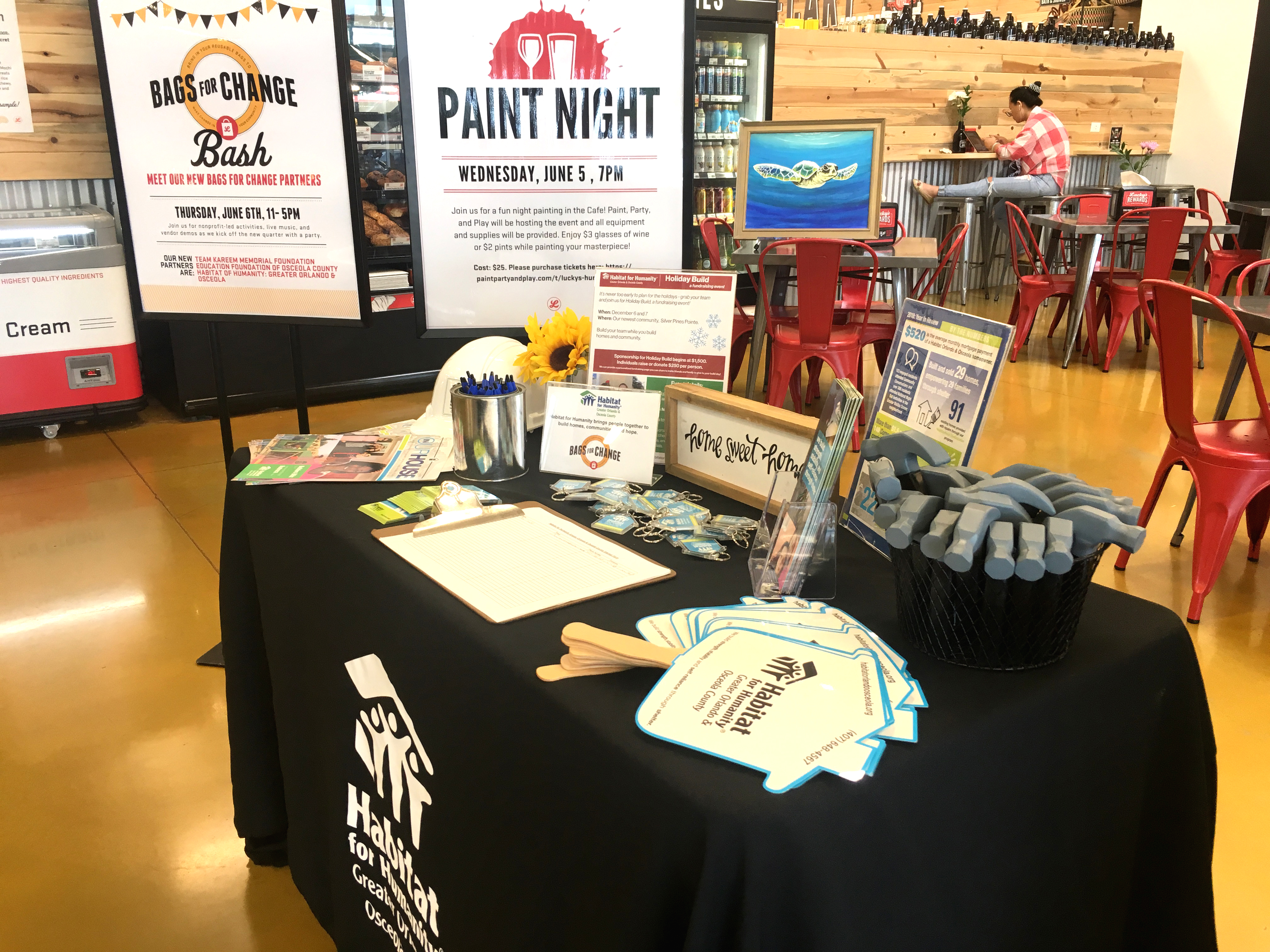Table in cafe in Lucky's Market with Habitat Orlando & Osceola fans, hammers and collateral displayed and event signage in the background