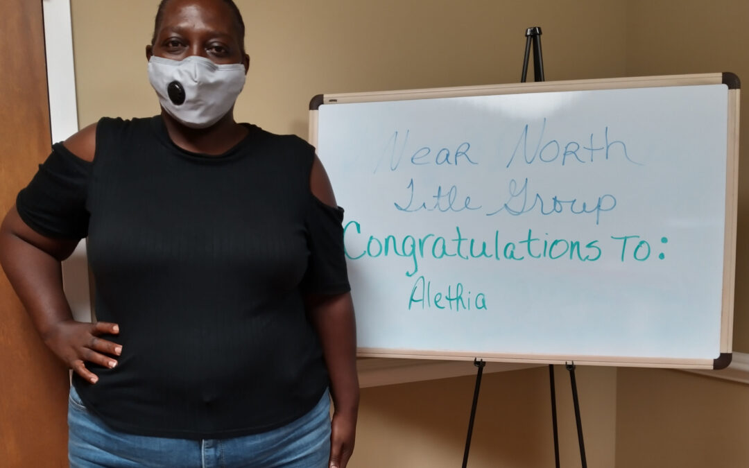 "A masked woman poses in front of a sign that reads, ""Near North Title Group congratulations to: Alethia"""