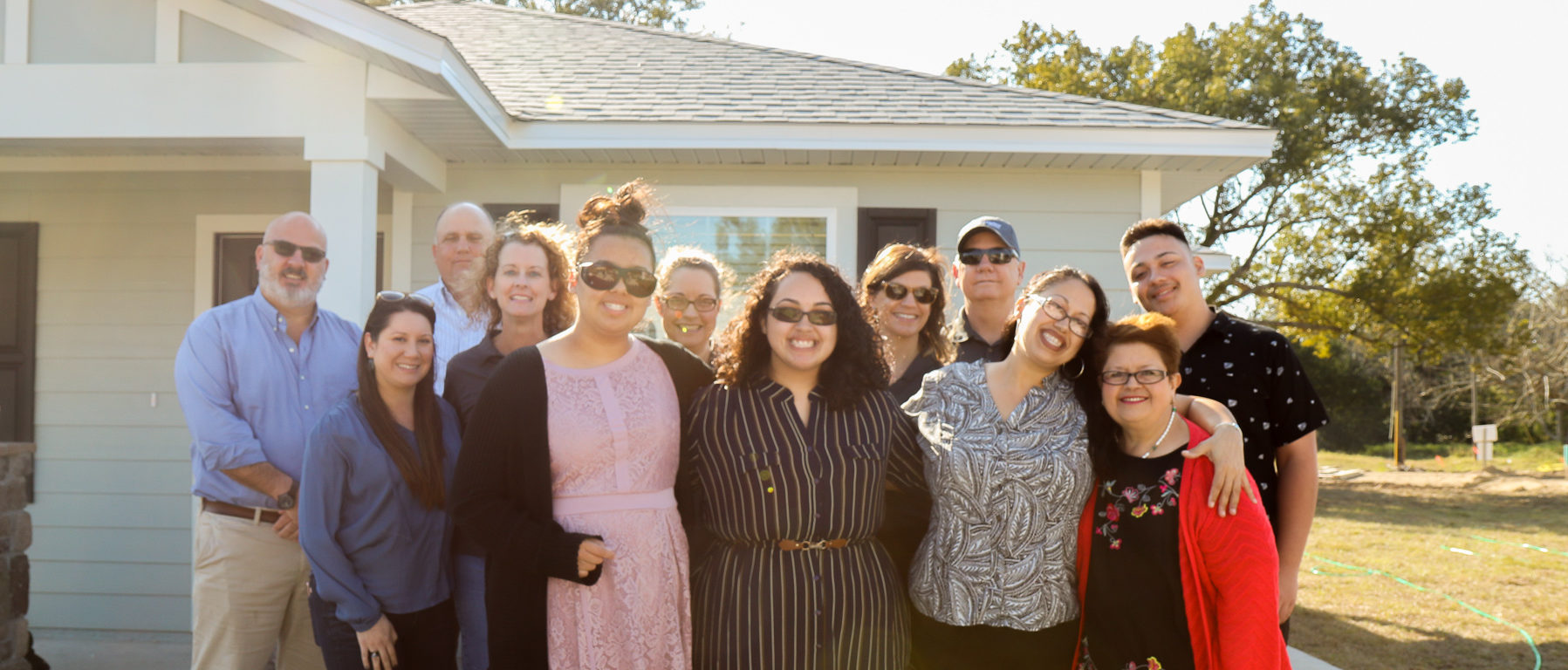 Large group of people with family in front and group of K. Hovnanian team members behind them, all in standing in front of newly completed house