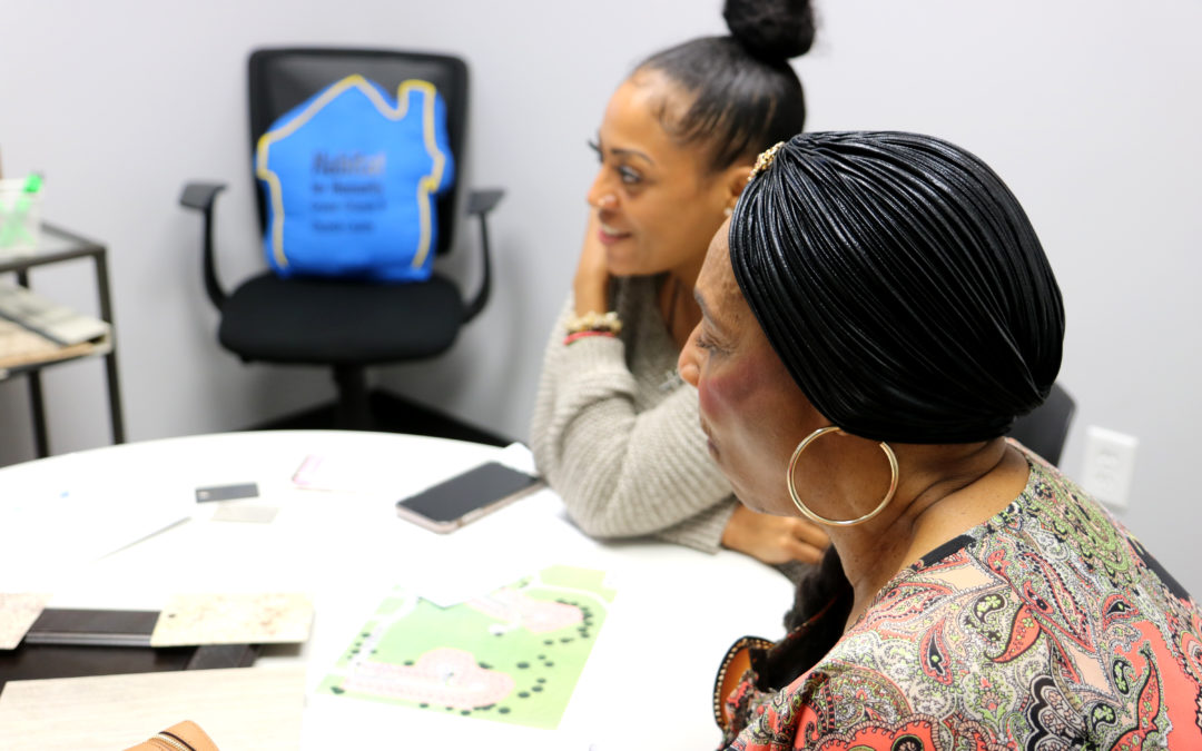 Two women sit at a table looking at house layouts.