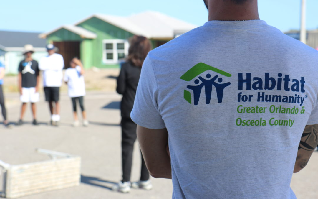A volunteer in a Habitat Orlando & Osceola T-shirt looks out into a construction site.