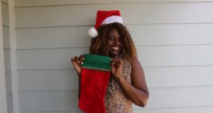 A woman holds a red stocking outside her home