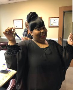 A woman celebrates her home's closing with her new keys in hand