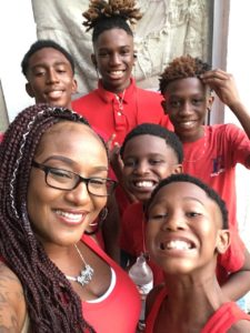 A woman and her five sons, all dressed in red, pose for a photo