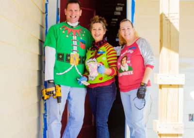 Group of three volunteers festively dressed and smiling in the doorway of an in-progress house
