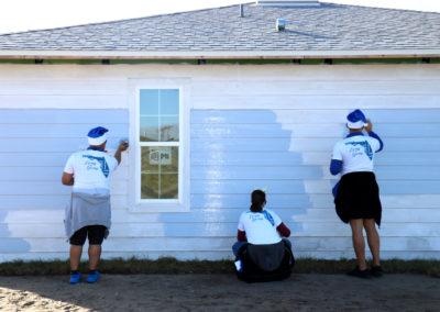 Three volunteers paint a house.