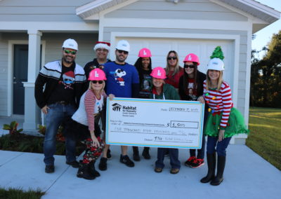 Holiday Build volunteers pose with their donation