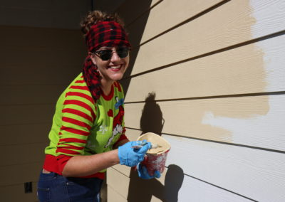 A volunteer poses while painting a house.