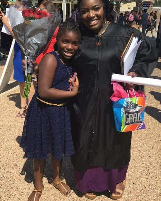 A mother dressed in graduation robes hugs her young daughter.