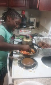 A child cooks vegetables on the stove.