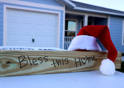 "Wood beam reading ""Bless this Home"" with a Santa hat resting on top, in front of completed house."