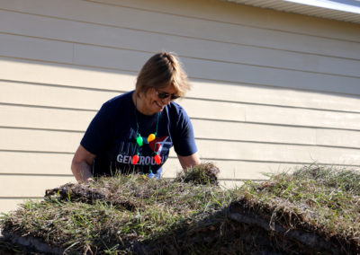 Volunteer smiling and reaching down to lift sod from pile